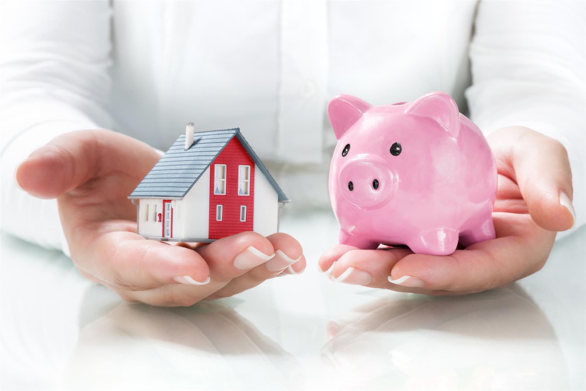 woman holds a piggy bank and a house model
